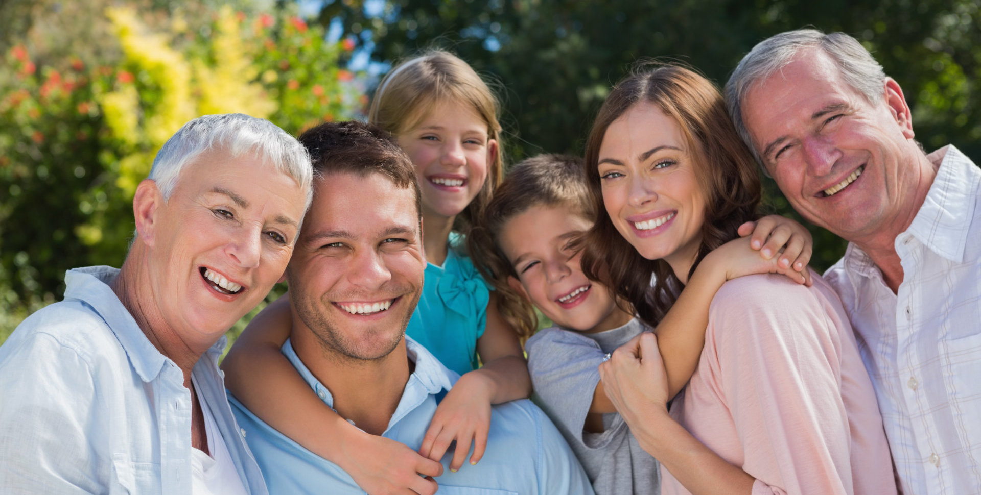Smiling family and grandparents in the countryside embracing and smiling at camera