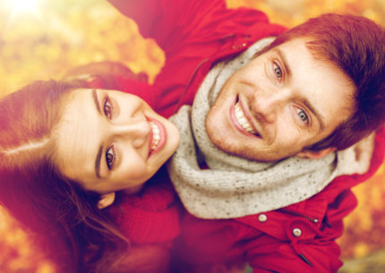 close up of happy smiling young couple taking selfie in autumn park
