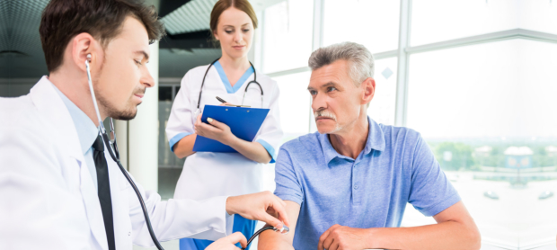 Male medical doctor examining his mature patient with stethoscope